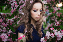 Portrait of a young curly-haired girl with closed eyes in a blue dress standing among a blossoming apple-tree. Clouse-up portrait of a young curly-haired girl Stock Photos