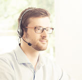 Portrait of a young customer support operator. Close-up portrait of young and confident customer support operator working in a call center office Stock Images