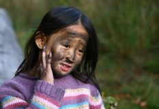 Portrait of a young cute girl looking at the camera putting coal royalty free stock photo