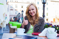 Portrait of young cute elegant woman sitting outdoor in a cafe i Stock Image