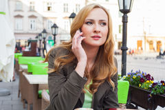 Portrait of young cute elegant woman sitting outdoor in a cafe i Royalty Free Stock Photography