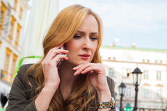 Portrait of young cute elegant woman sitting outdoor in a cafe i Stock Photography