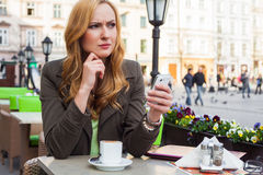 Portrait of young cute elegant woman sitting outdoor in a cafe i Royalty Free Stock Images