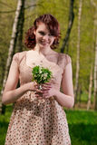 Portrait of young cute female with snowdrops Royalty Free Stock Images