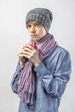 Portrait of young cute frozen teenager in a scarf and with tea cup. Portrait of young cute frozen teenager in a scarf and with red tea cup Royalty Free Stock Image