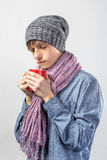Portrait of young cute frozen teenager in a scarf and with tea cup Royalty Free Stock Image