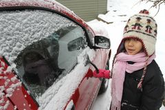 Portrait of a young cute girl looking at the camera romoving snow from a car royalty free stock photos