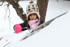 Portrait of a young cute girl looking at the camera romoving snow from a car stock photo