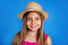 Portrait of young cute girl in pink dress and hat on blue background .Summer vacation and travel concept Royalty Free Stock Image