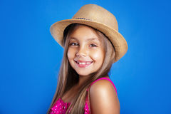 Portrait of young cute girl in pink dress and hat on blue background .Summer vacation and travel concept Stock Images