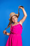 Portrait of young cute girl in pink dress and hat having fun on blue background .Summer vacation and travel concept Royalty Free Stock Images