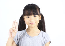 Portrait of young cute girl posting with thtee fingers. Royalty Free Stock Photography