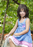 Portrait of young, cute girl sitting on wooden table in  dress, against background of summer green tree Royalty Free Stock Photos