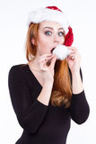 Portrait of a young cute red-haired girl in a shiny Christmas hat Royalty Free Stock Images