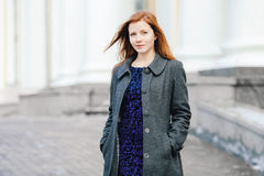 Portrait of young cute redhead woman in blue dress and grey coat  on the porch at winter outdoors Stock Photos