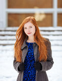 Portrait of young cute redhead woman in blue dress and grey coat at winter outdoors Stock Image