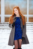 Portrait of young cute redhead woman in blue dress and grey coat at winter outdoors Royalty Free Stock Photos