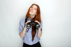 Portrait of young cute redhead woman  wearing blue striped shirt smiling with happiness and joy while posing with binoculars again. St white studio background Stock Images