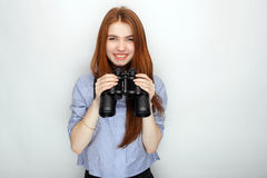 Portrait of young cute redhead woman  wearing blue striped shirt smiling with happiness and joy while posing with binoculars again Stock Photos