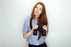 Portrait of young cute redhead woman  wearing blue striped shirt smiling with happiness and joy while posing with binoculars again. St white studio background Royalty Free Stock Photo