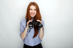 Portrait of young cute redhead woman  wearing blue striped shirt smiling with happiness and joy while posing with binoculars again. St white studio background Royalty Free Stock Photos