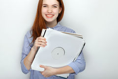 Portrait of young cute redhead woman wearing blue striped shirt smiling with happiness and joy while posing with vinyl records aga. Portrait of young cute Royalty Free Stock Image