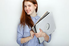 Portrait of young cute redhead woman wearing blue striped shirt smiling with happiness and joy while posing with vinyl records aga. Portrait of young cute Royalty Free Stock Images