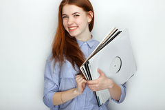 Portrait of young cute redhead woman wearing blue striped shirt smiling with happiness and joy while posing with vinyl records aga Stock Image