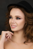 Portrait of young cute smiling woman wearing black hat Royalty Free Stock Images