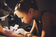 Portrait of a young cute woman master tattooist makes the tattoo on hand on a purplish blue likeness of a future tattoo Stock Images