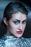 Portrait of young cyber woman in silver futuristic costume with bright makeup. Royalty Free Stock Photography