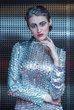 Portrait of young cyber woman in silver futuristic costume with bright makeup. Stock Photo