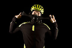 Portrait of young cyclist fully equipped for race in helmet and and mask. Black background. Close up Royalty Free Stock Photos