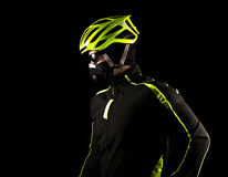 Portrait of young cyclist fully equipped for race in helmet and and mask. Black background. Close up Stock Images