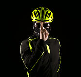 Portrait of young cyclist fully equipped for race in helmet and and mask. Black background. Close up Royalty Free Stock Images