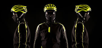 Portrait of young cyclist fully equipped for race in helmet and and mask. Black background. Close up Royalty Free Stock Image