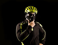 Portrait of young cyclist fully equipped for race in helmet and and mask. Black background. Close up Royalty Free Stock Photography