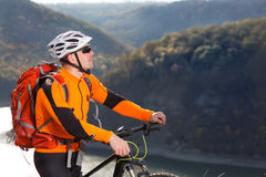 Portrait of young cyclist with a red backpack standing under river against summer landscape with mountain. Royalty Free Stock Images