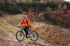 Portrait of young cyclist riding bicycle along trail in the countryside. Stock Photo