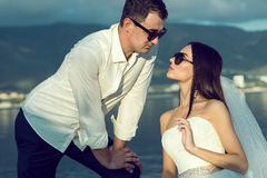 Portrait of a young dark-haired just married couple in stylish sunglasses and wedding gowns leaning to each other wishing to kiss Stock Photo