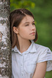 Portrait of young dark-haired woman embracing birch tree Royalty Free Stock Image
