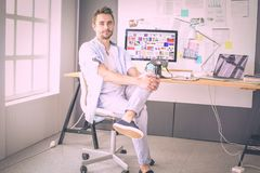 Portrait of young designer sitting at graphic studio in front of laptop and computer while working online. Portrait of young designer sitting at graphic studio royalty free stock image