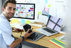 Portrait of young designer sitting at graphic studio in front of laptop and computer while working online. Portrait of young designer sitting at graphic studio stock photography