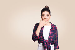 Portrait of young desperate woman in casual style amd bun hairstyle looking surprised, with mouth wide open and hands. Stock Image