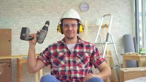 Portrait young disabled man in a wheelchair in a helmet and with an electric drill in his hand. Looking at the camera stock footage