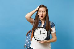 Portrait of young dissatisfied woman student with backpack clinging to head, holding alarm clock isolated on blue royalty free stock images