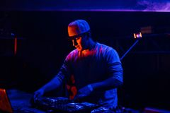 Portrait of a young Dj playing mixing music at night party. Under blue and red lights. Fun, youth, entertainment and fest concept Royalty Free Stock Photos