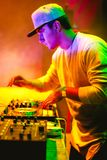 Portrait of Young DJ playing mixing music at night. Party under colorful lights. Fun, youth, entertainment and fest concept Stock Images