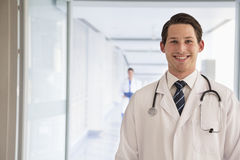 Portrait of young doctor in lab coat in the hospital, looking at camera Royalty Free Stock Images