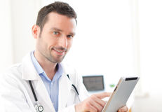 Portrait of a young doctor using tablet at work Stock Photography